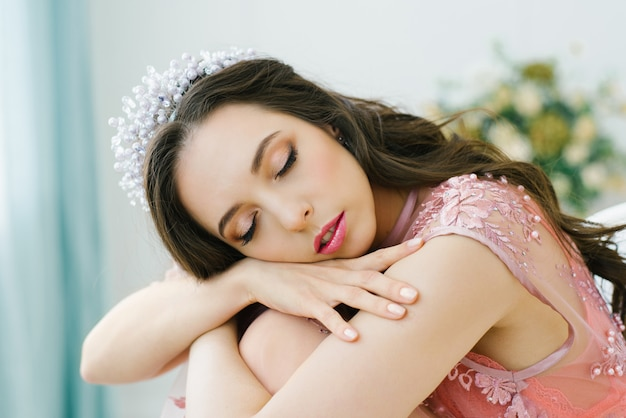 Retrato de uma jovem mulher bonita com os olhos fechados em um vestido rosa boudoir