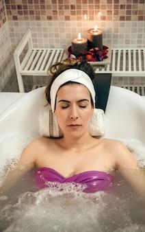 Retrato de uma jovem mulher bonita com turbante deitado na banheira, fazendo tratamento de hidroterapia. conceito de saúde e beleza.