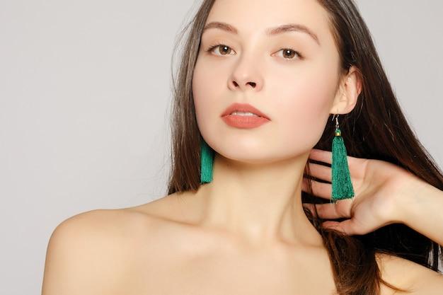 Retrato de uma jovem mulher bonita com uma pele perfeita e maquiagem brilhante, tocando seu rosto com os dedos bem cuidados. brincos compridos de tecido verde nas orelhas. seus ombros nus. fechar-se. cópia-espaço