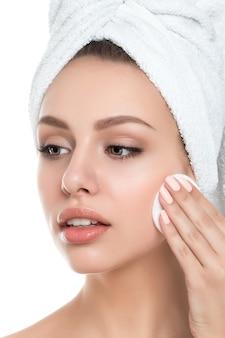 Retrato de uma jovem mulher bonita com uma toalha no cabelo, limpando a maquiagem do rosto com almofada cosmética isolada