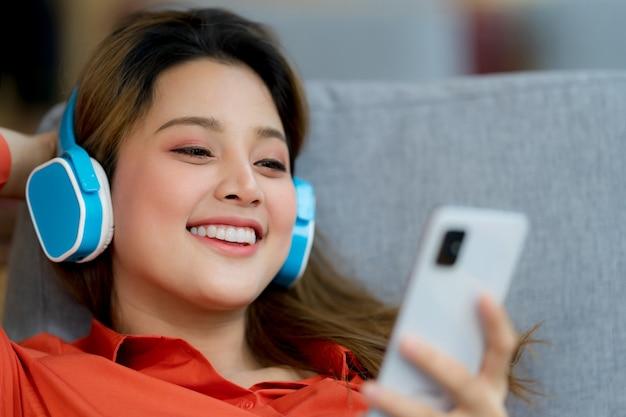 Retrato de uma jovem mulher bonita curtindo a música com uma carinha sorridente, sentado em um escritório criativo ou um café