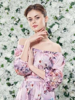 Retrato de uma jovem mulher bonita de flores em um vestido floral