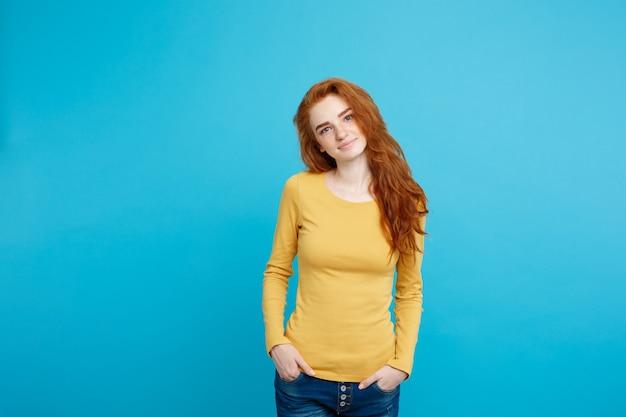 Retrato de uma jovem mulher bonita de gengibre com sardas sorrindo alegremente isolado no espaço de cópia da parede azul pastel