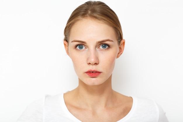 Retrato de uma jovem mulher bonita e. ela espia intensamente a distância. os olhos dela estão bem abertos.