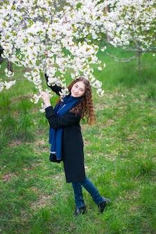 Retrato de uma jovem mulher bonita e elegante no parque de florescimento de primavera.