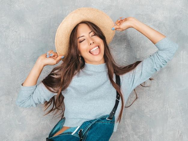 Retrato de uma jovem mulher bonita e sorridente com os olhos fechados. menina na moda em roupas de verão casual macacão e chapéu. e mostra a língua