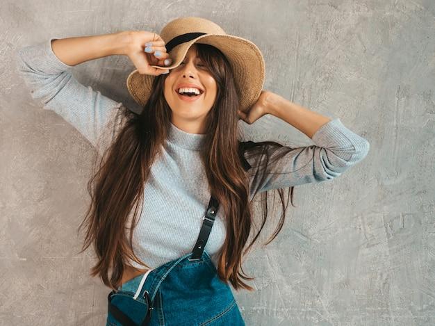 Retrato de uma jovem mulher bonita e sorridente com os olhos fechados. menina na moda em roupas de verão casual macacão e chapéu.
