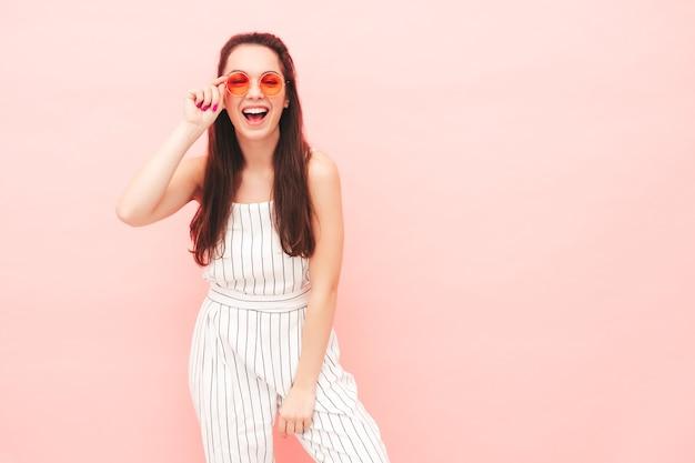 Retrato de uma jovem mulher bonita e sorridente em roupas de macacão moderno de verão moderno