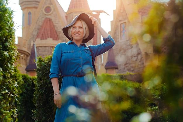 Retrato de uma jovem mulher bonita elegante feliz posando na rua contra a cidade velha medieval.