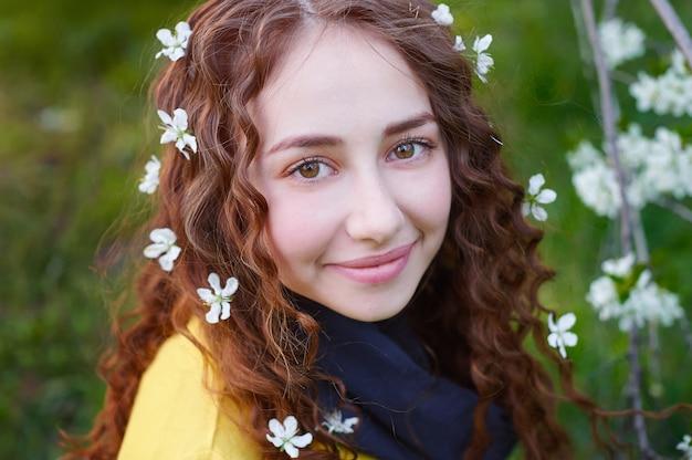 Retrato de uma jovem mulher bonita em árvores de flor de primavera