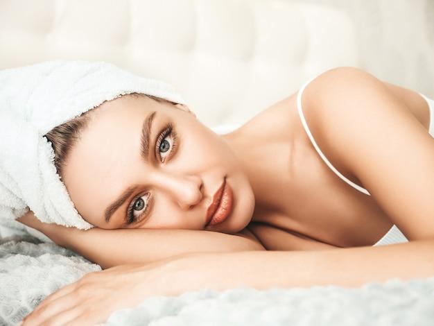 Retrato de uma jovem mulher bonita em lingerie branca e toalha na cabeça
