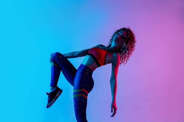 Retrato de uma jovem mulher bonita em roupas esportivas brilhantes, isolado em gradiente