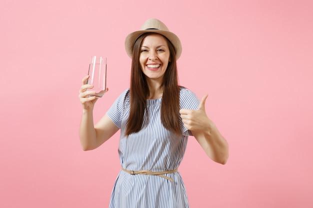 Retrato de uma jovem mulher bonita em um vestido azul, chapéu segurando e bebendo água pura fresca de vidro isolado no fundo rosa. estilo de vida saudável, pessoas, conceito de emoções sinceras. copie o espaço