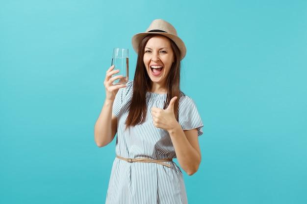 Retrato de uma jovem mulher bonita em um vestido azul, chapéu, segurando e bebendo água pura fresca de vidro isolado sobre fundo azul. estilo de vida saudável, conceito de emoções sinceras de pessoas. copie o espaço.