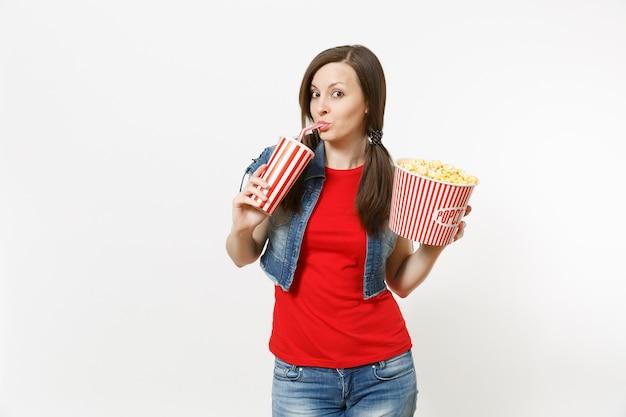 Retrato de uma jovem mulher bonita engraçada em roupas casuais, assistindo a um filme, segurando um balde de pipoca, bebendo em um copo plástico de refrigerante ou coca-cola, isolado no fundo branco. emoções no cinema.