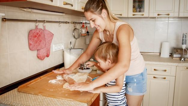 Retrato de uma jovem mulher bonita ensinando seu filho filho a fazer biscoitos e assar tortas na cozinha em casa