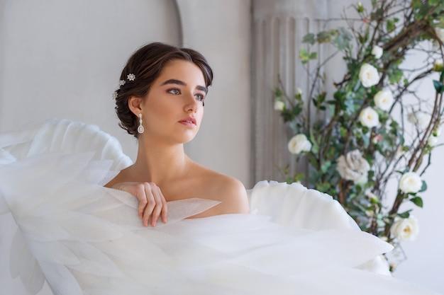 Retrato de uma jovem mulher bonita envolta em asas de anjo branco.