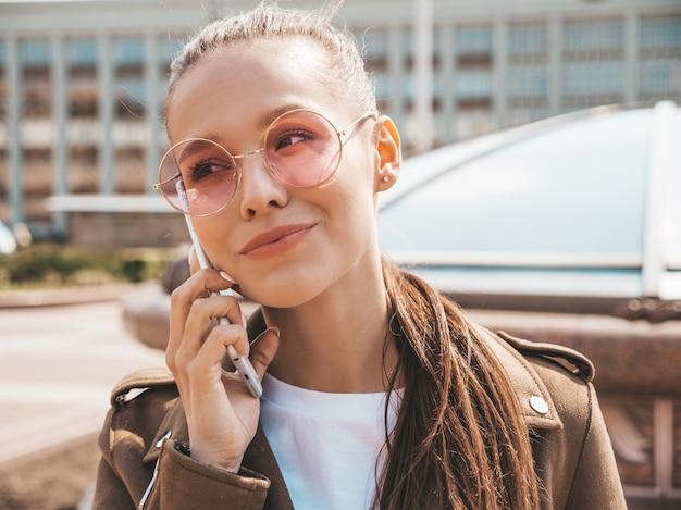 Retrato de uma jovem mulher bonita falando no telefone menina na moda em roupas de verão casual engraçado e positivo feminino posando na rua