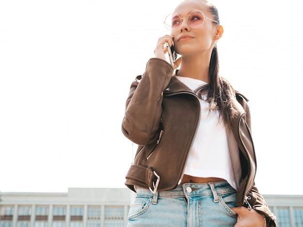 Retrato de uma jovem mulher bonita falando no telefone menina na moda em roupas de verão casual mulher séria posando na rua