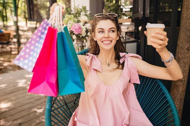Retrato de uma jovem mulher bonita feliz e sorridente com expressão de rosto animado, sentado no café com sacolas de compras, bebendo café