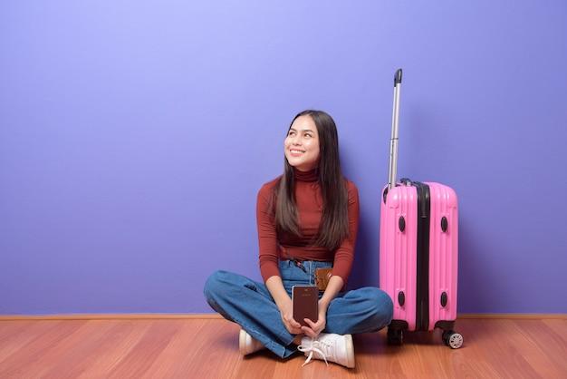 Retrato de uma jovem mulher bonita feliz está viajando a bordo com passaporte sobre roxo isolado