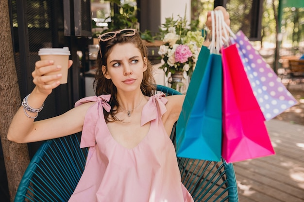 Retrato de uma jovem mulher bonita feliz sorridente com expressão de rosto animado, sentado no café com sacolas de compras, bebendo café