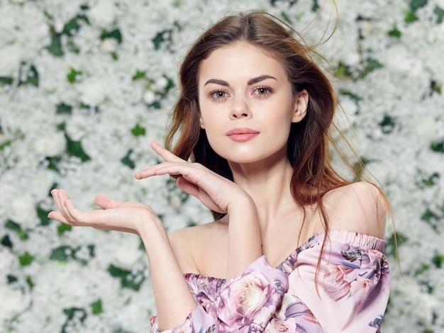 Retrato de uma jovem mulher bonita, flores em um vestido floral
