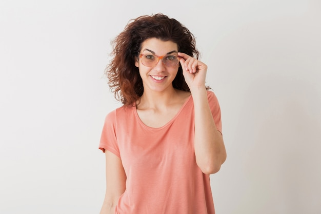 Retrato de uma jovem mulher bonita hippie natural com penteado encaracolado em uma camisa rosa posando usando óculos isolados no fundo branco do estúdio, expressão de rosto animado