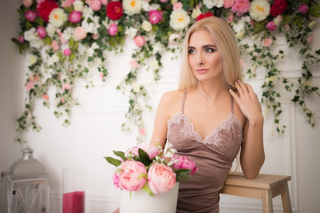 Retrato de uma jovem mulher bonita loira concurso posando num contexto de flores de cores vivas embaçadas e uma parede branca. conceito de feminilidade e beleza