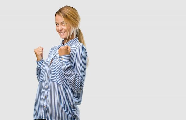 Retrato de uma jovem mulher bonita loira muito feliz e animado, levantando os braços