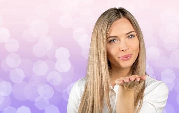 Retrato de uma jovem mulher bonita mandando beijo na câmera