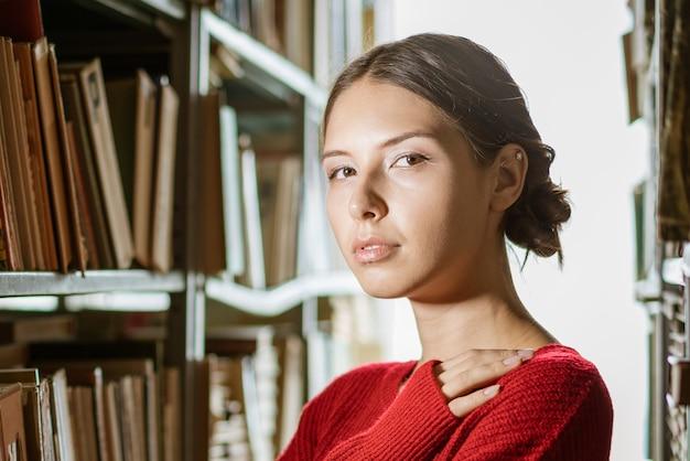 Retrato de uma jovem mulher bonita na biblioteca