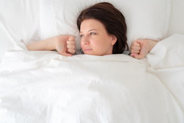 Retrato de uma jovem mulher bonita na cama, estendendo-se depois de acordar