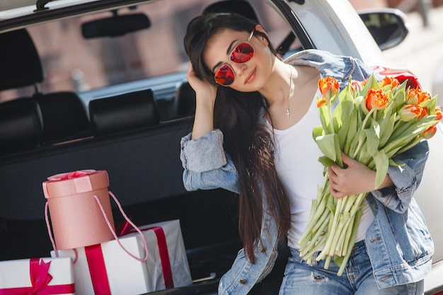 Retrato de uma jovem mulher bonita na primavera, segurando um buquê de flores frescas.