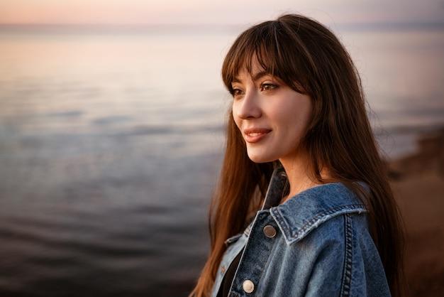 Retrato de uma jovem mulher bonita no fundo do mar ao pôr do sol