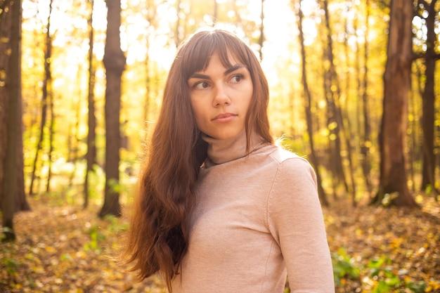 Retrato de uma jovem mulher bonita no parque outono no sol brilha jovem pensativa