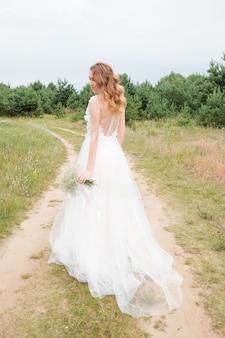 Retrato de uma jovem mulher bonita no vestido de casamento branco ao ar livre