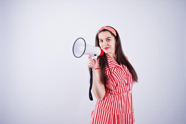 Retrato de uma jovem mulher bonita no vestido vermelho, falando no megafone.