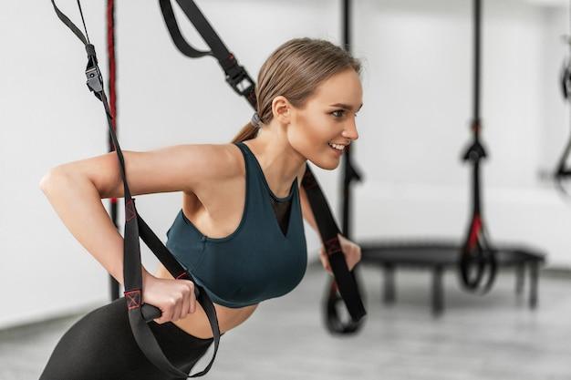 Retrato de uma jovem mulher bonita nos braços de treinamento de roupas esportivas com alças trx fitness na academia fazendo flexões