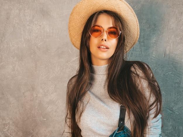 Retrato de uma jovem mulher bonita olhando. menina na moda em roupas de verão casual macacão e chapéu. em óculos de sol