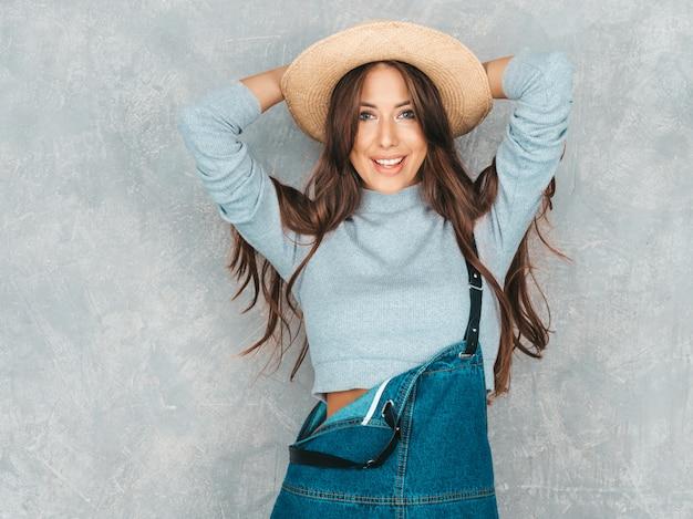 Retrato de uma jovem mulher bonita olhando. menina na moda em roupas de verão casual macacão e chapéu.