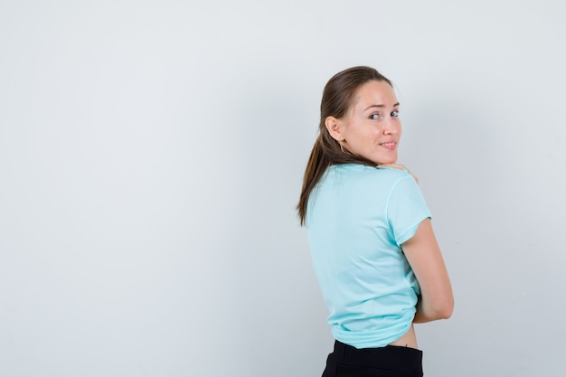 Retrato de uma jovem mulher bonita olhando por cima do ombro em uma camiseta e parecendo alegre