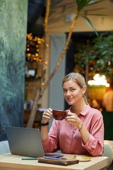 Retrato de uma jovem mulher bonita para uma pausa para o café enquanto está sentado à mesa em frente ao laptop na cafeteria