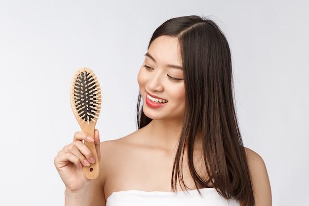 Retrato de uma jovem mulher bonita pentear o cabelo maravilhoso, isolado no fundo branco, beleza asiática