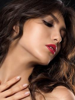 Retrato de uma jovem mulher bonita posando sobre fundo escuro. bronzeado claro e maquiagem de verão.