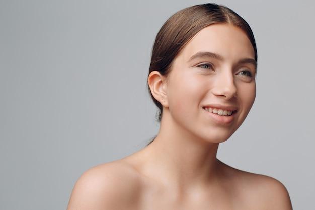 Retrato de uma jovem mulher bonita positiva com maquiagem nude.