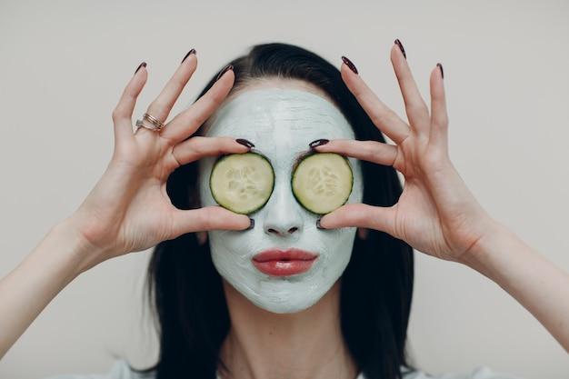 Retrato de uma jovem mulher bonita recebendo máscara facial de argila com pepino nos olhos em um salão de beleza spa