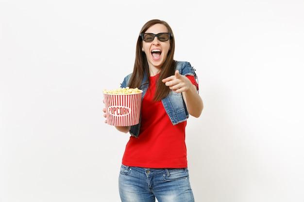 Retrato de uma jovem mulher bonita rindo em óculos 3d imax, assistindo a um filme, segurando um balde de pipoca e apontando o dedo indicador na câmera, isolada no fundo branco. emoções no conceito de cinema.