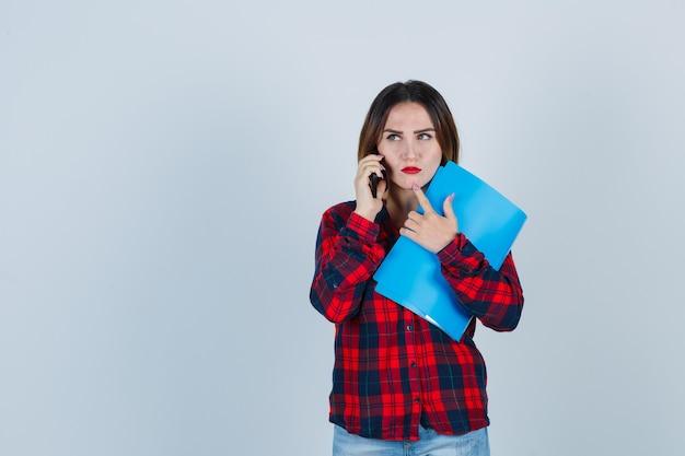 Retrato de uma jovem mulher bonita segurando a pasta enquanto fala no telefone, tocando o queixo com o dedo em uma camisa casual, jeans e olhando pensativa com vista frontal