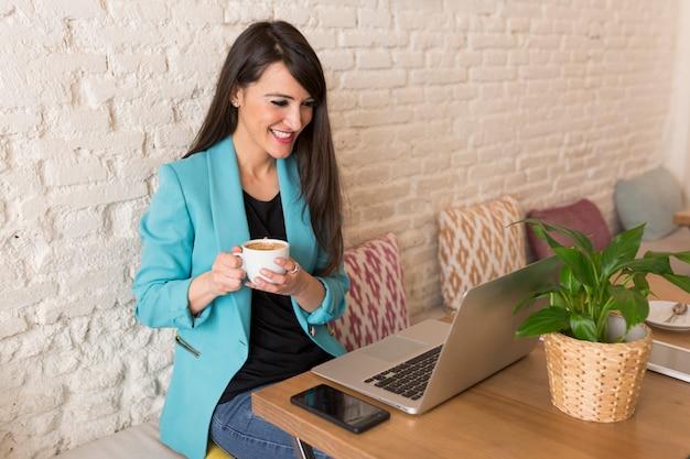 Retrato de uma jovem mulher bonita segurando café em um restaurante. ela está sorrindo. vida moderna de um blogueiro com computador laptop, celular, tablet e notebook em cima da mesa. casual. estilo de vida